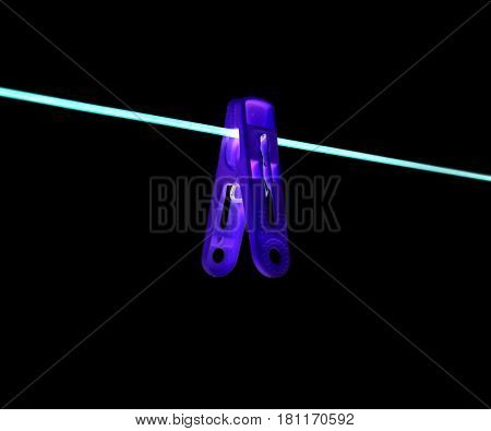Clothespin on a rope on a black background .