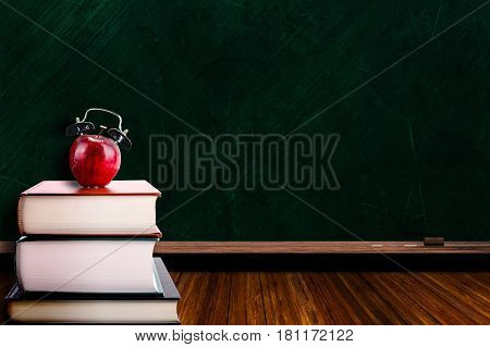 Apple Alarm Clock On Stack Of Books And Chalkboard Background