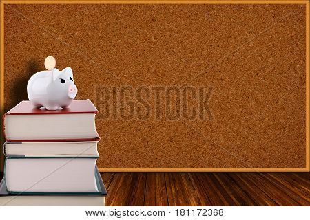 Piggy Bank On Stack Of Books And Corkboard Background