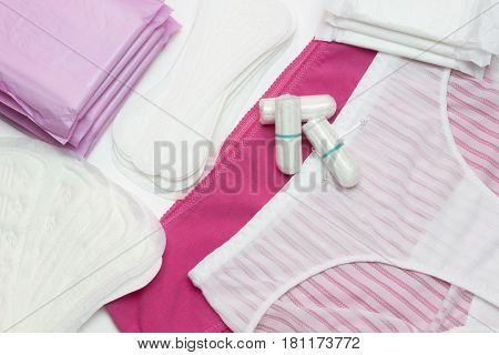 Menstruation sanitary pads and cotton tampons for woman hygiene protection. White and pink pants. Soft and tender protection for woman critical days gynecological menstruation cycle