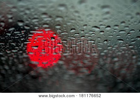 Abstract background for the banner. One night lights of city transport were seen through the windshield in rainy weather. Concept of threat, danger, hazard, peril, menace, jeopardy, imminence