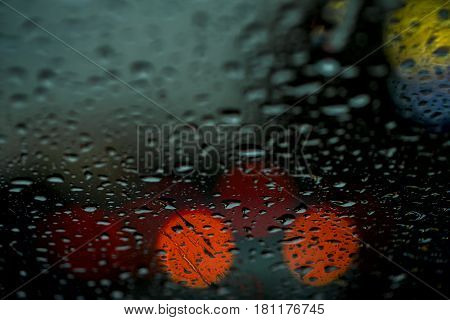 Night view of the city lights through the window in the rain, rain drops falling on the windshield of the car. Abstract light bokeh, defocused background for banner design