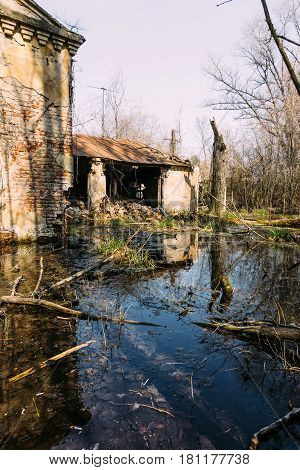 Old destroyed and abandoned house is flooded with water, can be used as demolition, earthquake or natural disaster concept. Housing left by people. Reflection in water, vertical image, free copy space
