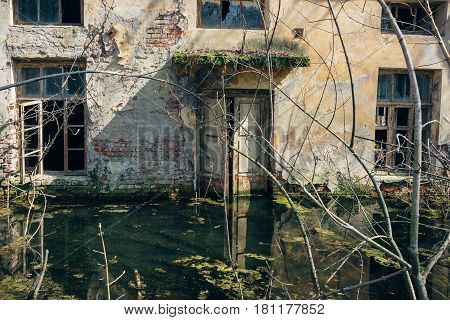 Old abandoned house with peeling walls is flooded with water