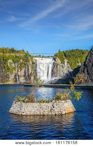 Small picturesque artificial island on the lake. Montmorency Falls Park, in Quebec.  Above the waterfall built bridge for walking. The concept of active and cultural tourism