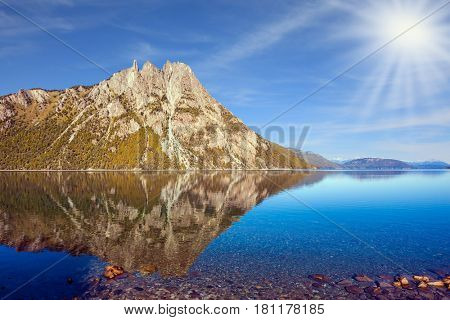 Picturesque mountain and lake in Bariloche, Argentina. The concept of exotic and extreme tourism. The summer sun illuminates the picturesque landscape