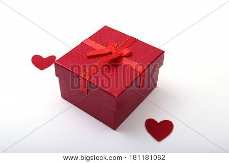 Beautiful red present, gift box with red bow and heart on white backgound