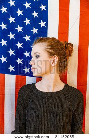 Young gender fluid girl looking away in front of US stars and stripes flag vintage color.
