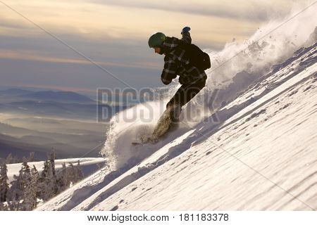 Fast snowboarder downhill in powder. Extreme slope winter ski sports