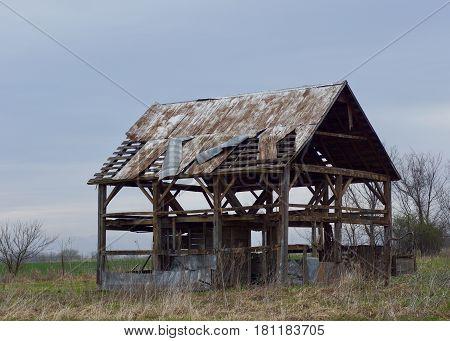 Old vintage barn in disrepair with water pump in foreground and grey skies.
