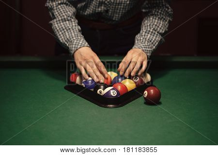 American billiard poule. Triangle of billiard balls. A woman getting ready to start a game of billiards.