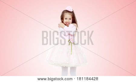 Dressy little girl long blonde hair, beautiful pink dress and a rose in her hair.She got cold.Pale pink gradient background.