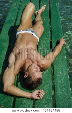 Attractive young, athletic muscle man laying down on a wood pier, looking at camera