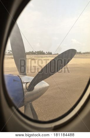 Engine propeller of a turboprop aircraft seen through the window from inside the cabin of an airplane on the ground