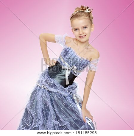Slender little girl , with beautiful hair on his head, elegant long Princess dress.The girl twisted to the side and keeps his hand on his knee.Pale pink gradient background.