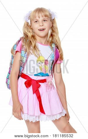 Happy little girl in a pink short skirt with a knapsack on his shoulders. Close-up-Isolated on white background