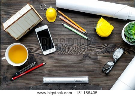 profession concept with architect desk and constructor tools and phone on wooden background top view