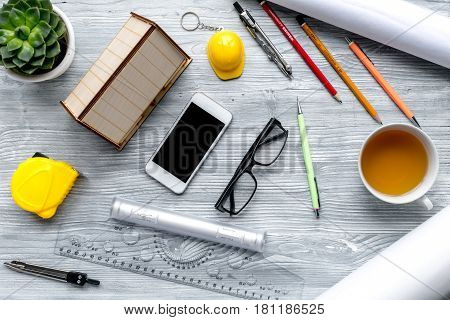 architect office with tools, cup and mobile in profession concept on light wooden desk background top view
