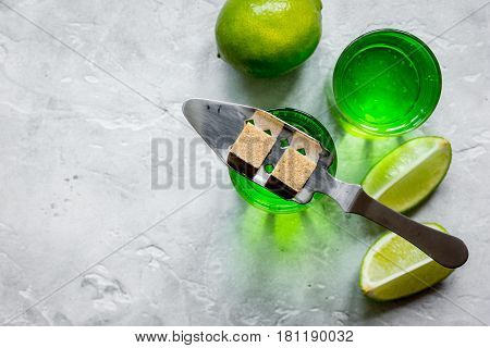 green absinthe in glass with fresh lime slices on stone table background top view mockup