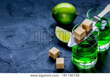 absinthe shots with fresh green lime slices and sugar cubes on dark bar table background mockup