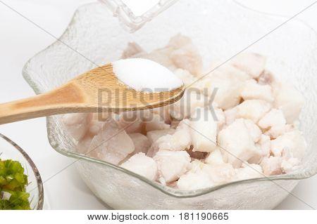 Peruvian ceviche preparation : Add salt to the marinated fish