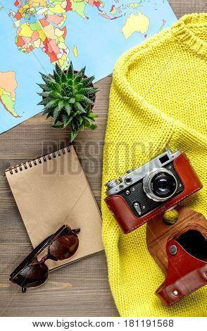 tourist stuff with photo camera and wordwide map on wooden table background top view