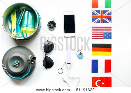 Outfit for trip with compass and mobile phone on white table background top view