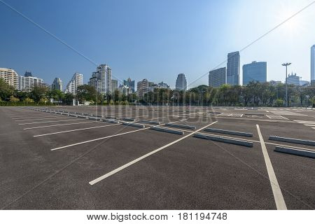 Empty parking lot at city center with blue sky and sun reflection