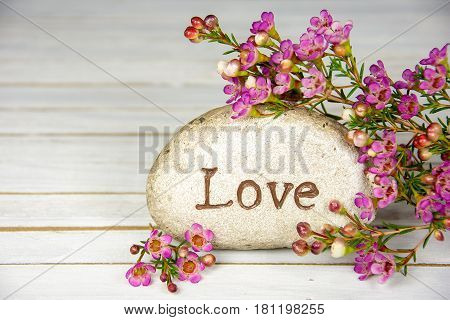 word love on stone with pink flowers and whitewashed wood