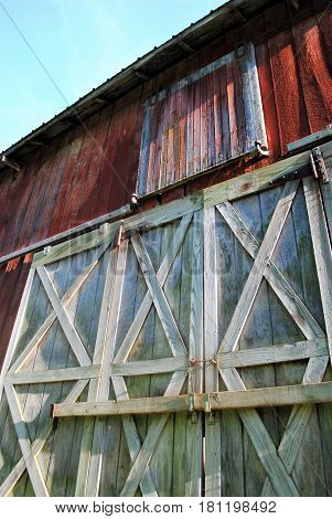 An abandoned red barn, beautiful doors closed.