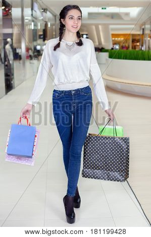 Beautiful girl walks in the Mall with gift bags. Smiling posing for the camera. To make purchases