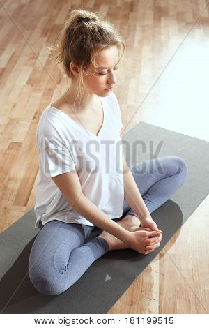 Hatha yoga. Yoga. A woman is practicing yoga on a mat.