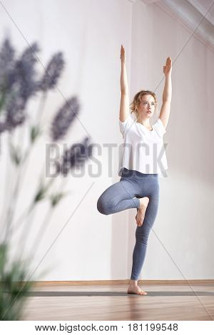 Hatha yoga. Yoga. A woman is practicing yoga on a mat.