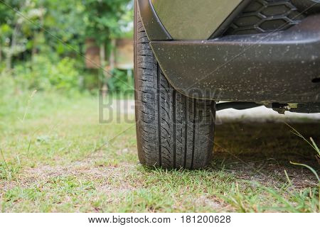 The Front tire of cars parked on grass.