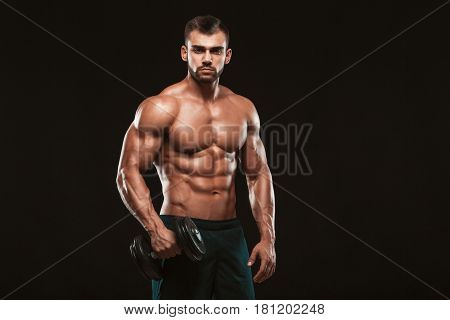 Handsome power athletic man in training pumping up muscles with dumbbells in a gym. Fitness muscular body isolated on dark background