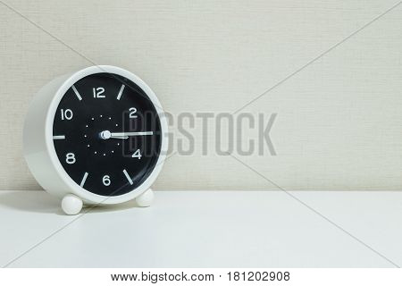 Closeup black and white alarm clock for decorate show a quarter past three o'clock or 3:15 p.m.on white wood desk and cream wallpaper textured background with copy space