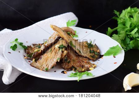 Fried oyster mushrooms with garlic, parsley in a balsamic glaze on a black background. Healthy eating concept.