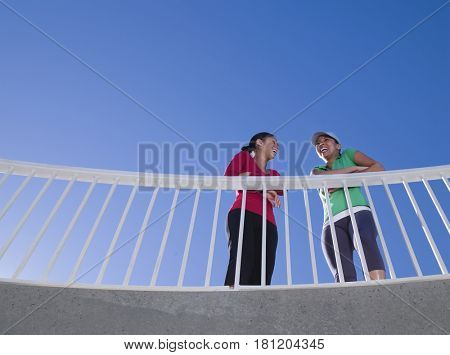 Multi-ethnic women leaning on railing
