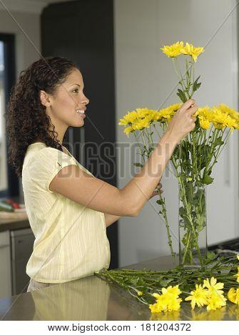 Mixed Race woman arranging flowers