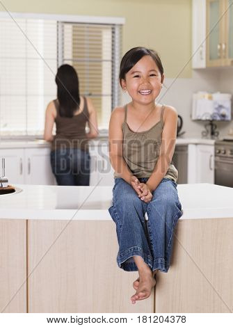 Mixed Race girl sitting on kitchen counter