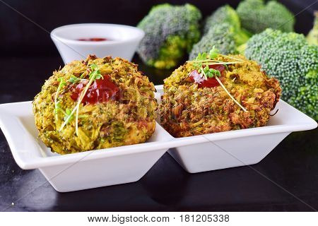 Broccoli balls deep fried on a white plate with tomato sauce with fresh broccoli on a black abstract background. Healthy eating concept. Dieting