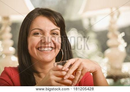 Hispanic woman holding glass