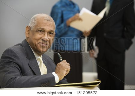 Senior African businessman holding pen
