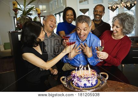 Hispanic man celebrating birthday with multi-ethnic friends