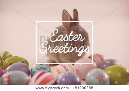 Easter greeting against easter eggs with cute easter bunny