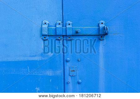 Close-up old blue door hinge on metal door