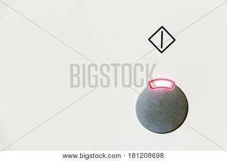 Closeup power button with burning red light and symbol above it on white background