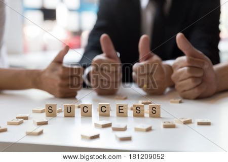 Word ''success'' on wooden letters blocks with business team group giving thumbs up