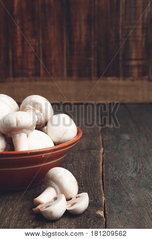 Fresh White Mushrooms Champignon In Brown Bowl On Wooden Background. Top View. Copy Space.