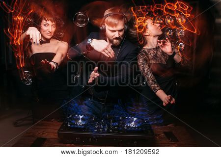 Two beautiful young girls dancing with handsome bearded disk jockey at DJ console. Party, dance, music, relax, light long exposure